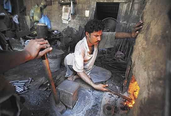 Paquistanês perto de forno a carvão: a poluição em casa mata mais que a externa (Akhtar  Soomro/Reuters - 28/3/11)