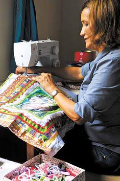 Rozeli Costa faz os estandartes num quarto de sua casa. Junta tecidos e fitas coloridas, imagens de santos, mas não sabe o preço   (Janine Moraes/CB/D.A Press)
