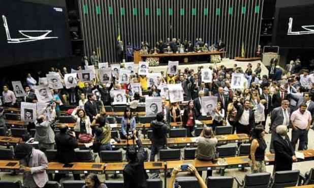 Integrantes de movimentos sociais ficam de costas para a tribuna da Câmara: solenidade interrompida (Sérgio Lima/Folhapress)