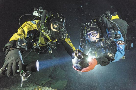 Mergulhadores seguram o crânio de Naia, que caiu na caverna há 12 mil ou 13 mil anos. O rosto da jovem será reconstituído no próximo mês  (Fotos: Paul Nicklen/National Geographic)