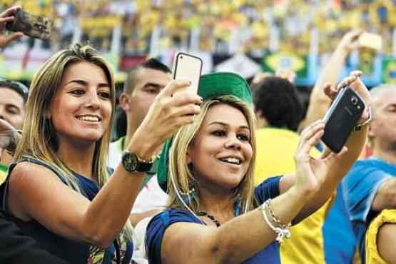 Torcedoras tiram foto na estreia da Sele��o: 90% dos espectadores devem compartilhar experi�ncias na rede