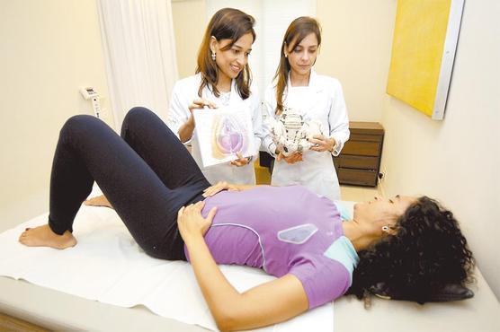 As fisioterapeutas Sabrina e Renata auxiliam a paciente Karen a fazer exercícios e posições que podem fortalecer os músculos do períneo (Jair Amaral/EM/D.A Press)