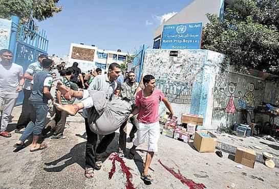 Palestinos transportam um ferido no ataque � escola: