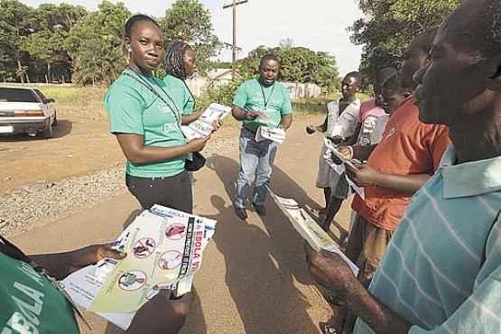 Volunt�rios distribuem panfletos com orienta��es a moradores de Monr�via, capital da Lib�ria: v�rus j� matou 255 pessoas no pa�s desde mar�o (Samaritan's Purse/Reuters)