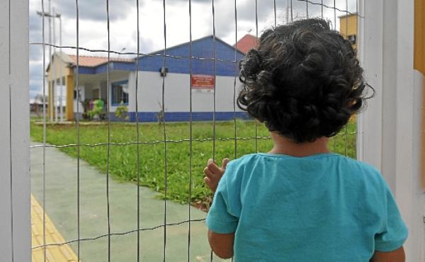 Pelo port�o, crian�a observa uma creche fechada em  Samambaia  (Minervino Junior/CB/D.A Press - 1/12/14 )