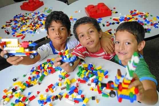 Ismael, Paulo Eduardo e Erick aproveitam o tempo a mais na escola para se divertir na sala de robótica.