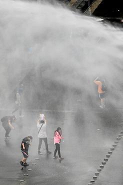 Manifestantes reagem a jato d'água disparado por blindado, em Santiago (Martin Bernetti/AFP)