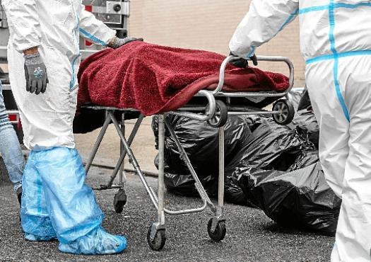 Funcionários transportam corpo do lado de fora de funerária do Brooklyn, em Nova York: metrópole contabilizava, até ontem, 19.057 mortes  (Johannes Eisele/AFP )