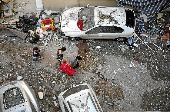 Moradores do bairro de Mar Mikhael, no centro de Beirute, abandonam apartamento com uma única mala nas mãos, em meio ao cenário de devastação (Patrick Baz/AFP)