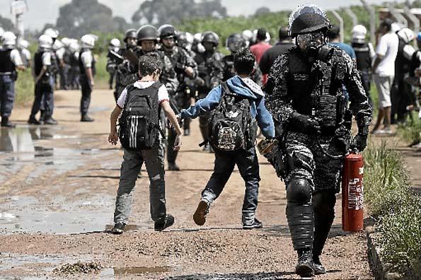 Policiais transitam entre meninos estudantes para garantir a derrubada, at� sexta-feira, dos 460 barracos constru�dos numa favela em meio a duas favelas: a Nova Jerusal�m, entre o Sol Nascente e o P�r do Sol.  (Marcelo Ferreira/CB/D.A Press)